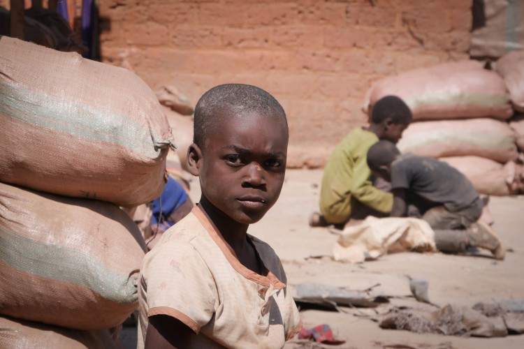 Dans le quartier de Kasulo,  les enfants jouent avec les sacs vides, auparavant remplis de minerais.